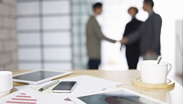 close-up of business items with people meeting in background.