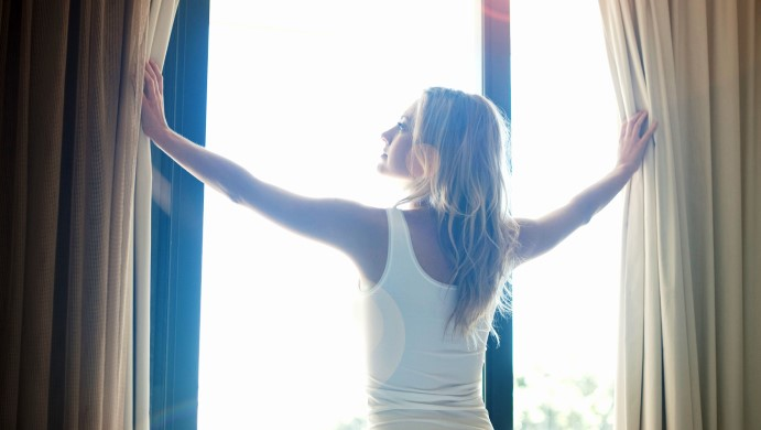 Woman opening curtains in bedroom