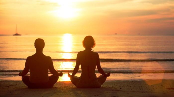 A young couple sitting on the beach of the sea in the lotus position at sunset, yoga practice; Shutterstock ID 130813172; PO: aol; Job: production; Client: drone