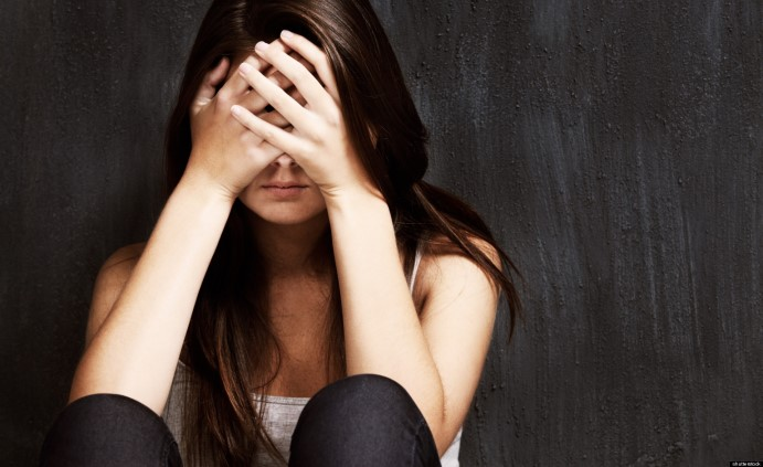 A studio shot of a sad young woman holding her head in her hands; Shutterstock ID 121515724; PO: The Huffington Post; Job: The Huffington Post; Client: The Huffington Post; Other: The Huffington Post