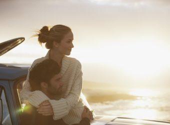 Serene couple hugging on truck at beach