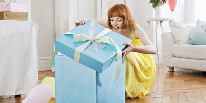 Woman opening large present.