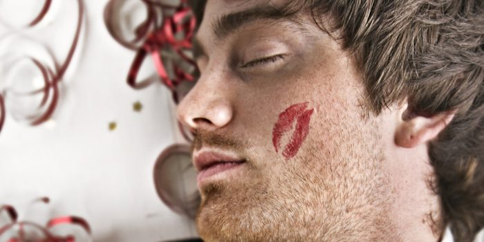 Man Sleeping on Party Floor with Cheek Lipstick Kiss