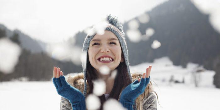 Happy woman enjoying falling snow in field
